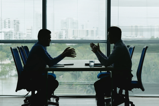 Outlines of two men talking in office